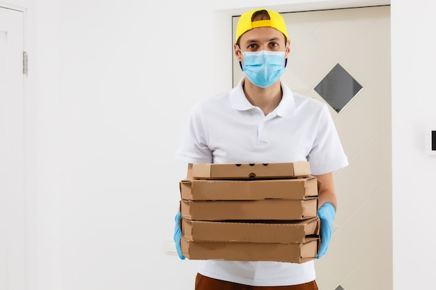 非接触ピザの配達。ピザボックス。医療用ゴム手袋とマスクで段ボール箱を保持している配達人。高速で無料の配達輸送。オンラインショッピングと速達。検疫