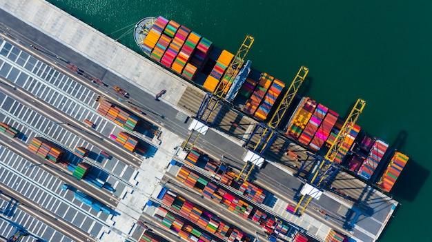 コンテナーターミナルで働くクレーン橋の排出を持つコンテナー貨物貨物船、深海港で空中の上面図コンテナー船。