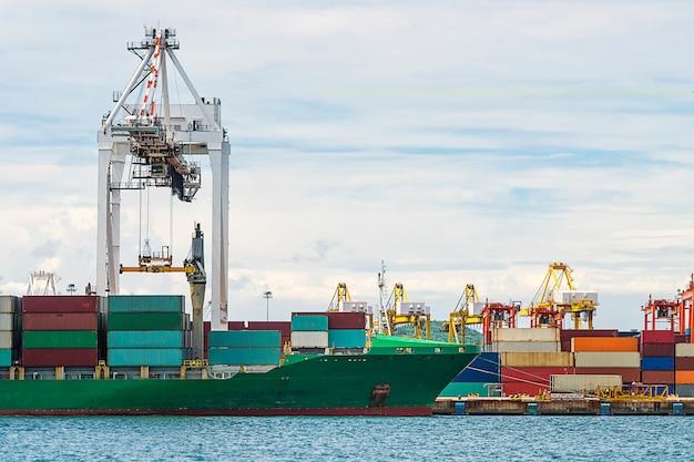 ロジスティックインポートエクスポートの夕暮れ時に造船所でクレーンブリッジが動作しているコンテナ貨物貨物船