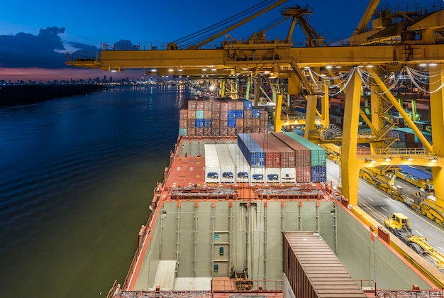 インポートエクスポートロジスティクスで造船所のクレーン橋が動作しているコンテナー貨物貨物船