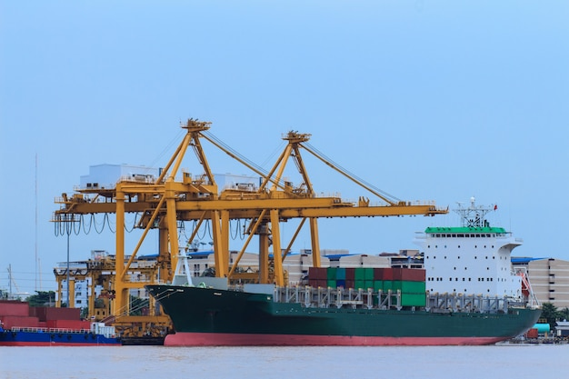 Container cargo freight ship with working crane bridge in shipyard at dusk f