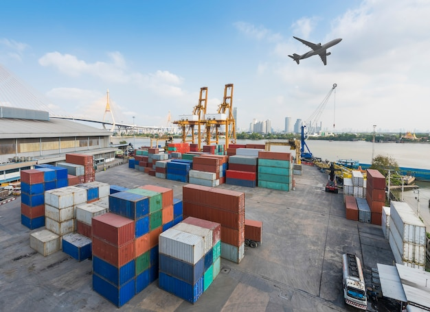 Container cargo freight ship with working crane bridge in shipyard in import export logistic zone