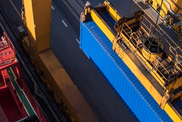 ロジスティックインポートエクスポートの夕暮れ時に造船所でクレーンロードブリッジが動作するコンテナー貨物貨物船