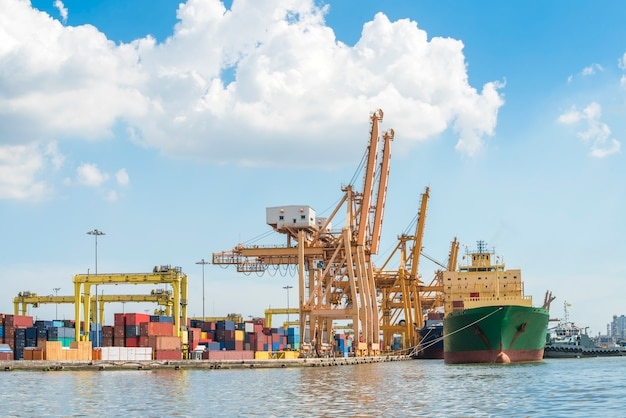 Container cargo freight ship with working crane loading bridge in shipyard for logistic import export
