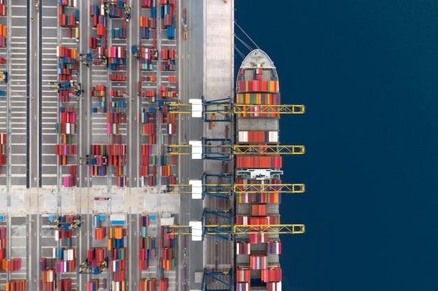 Погрузка контейнеровозов в порту, грузовые перевозки, импорт, экспорт и бизнес-логистика контейнеровозом, вид с воздуха.