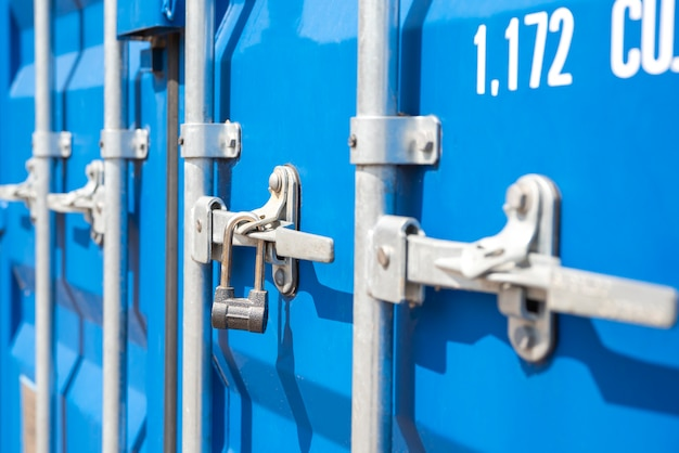 Container closeup blue cargo container with a lock the concept of the increased cost of freight bann...