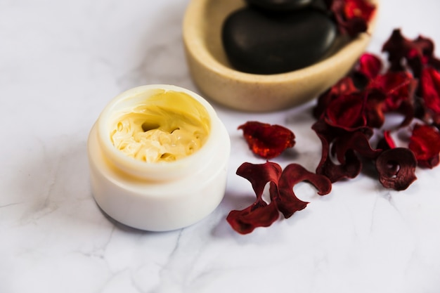 Container of cosmetic moisturizing cream with red orchid petals