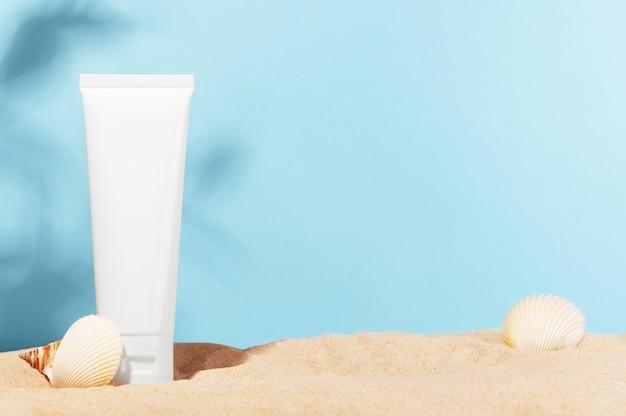 조개 껍질과 모래가있는 해변의 영양 또는 보습 크림, 마스크, 로션 용기
