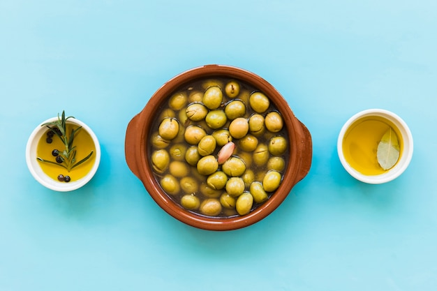 Container of green olives with bowl of oils on blue background