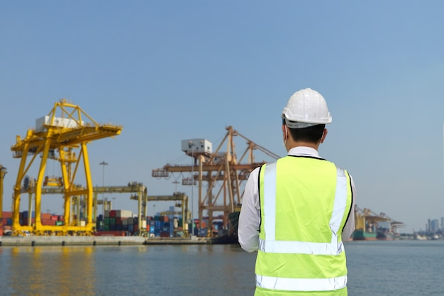 Container port, foreman and insurance claim officer checking on containers condition.