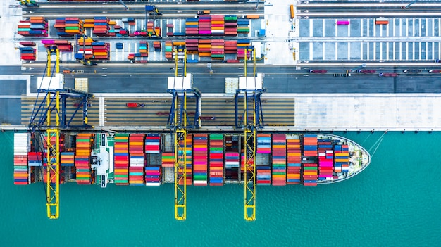 Container ship arriving in port, container ship loading at deep sea port, logistic business import export shipping and transportation, aerial view.