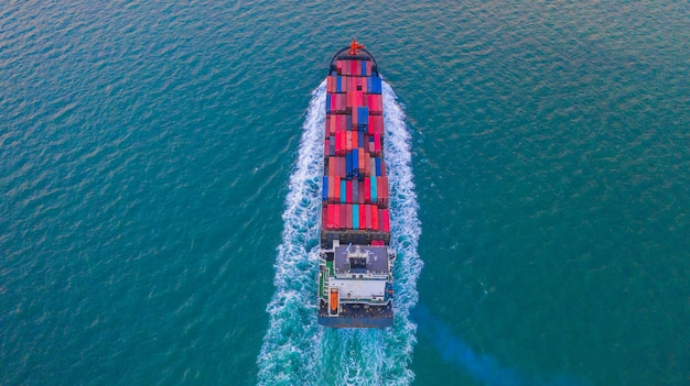 Container ship carrying container box for import and export business logistic and transportation by container ship in open sea, aerial view.