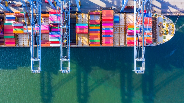 Container ship loading and unloading in deep sea port, aerial top view of business logistic import and export freight transportation