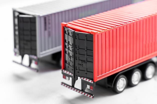 白い背景に選択的に焦点を当てたコンテナトラック、倉庫でのトレーラーコンテナトラックの駐車、グローバルビジネスロジスティックおよび輸送輸送会社。