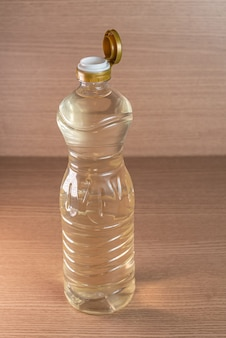 Container of vinegar on the wooden background