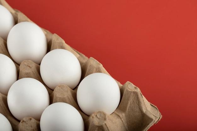 Contenitore di uova bianche sulla superficie rossa.