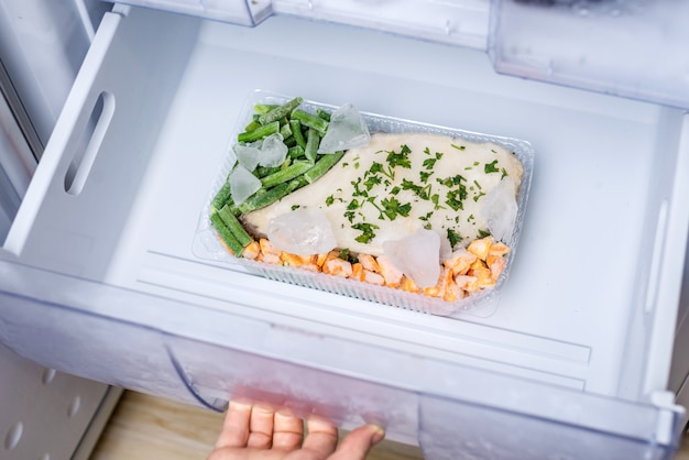 Container with frozen vegetables and fish in the freezer of the fridge