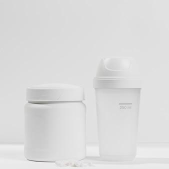Contenitore con supplementi di palestra e bottiglia