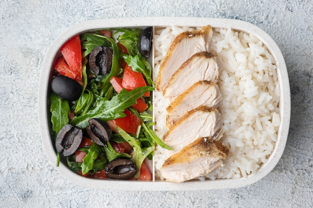 Container with natural healthy lunch, food box with rice, baked chicken breast, salad.
