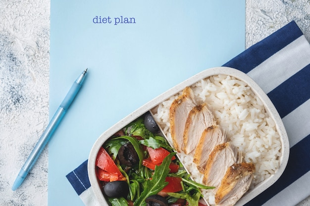 Container with natural healthy lunch, food box with rice, baked chicken breast, salad