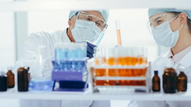 Контейнер с пробирками на столе в лаборатории.
