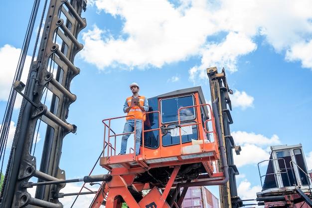Работник контейнеровоза работает и проверяет на складе контейнеров.