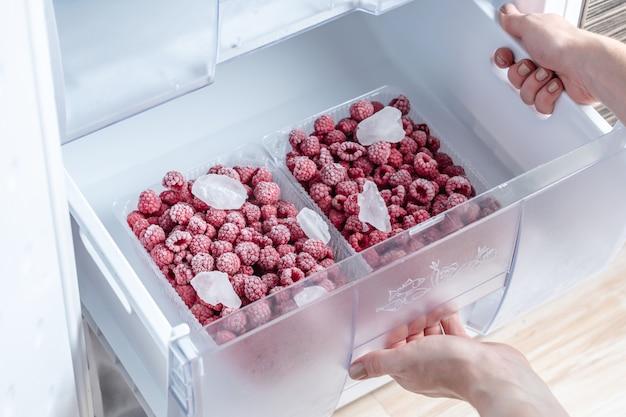 冷蔵庫の冷凍庫で冷凍ラズベリーが入った容器