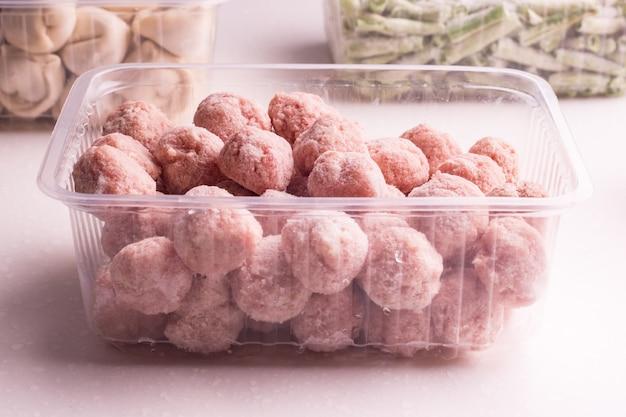 Контейнеры с замороженными мясными полуфабрикатами из холодильника. тефтели, пельмени, нарезанная фасоль