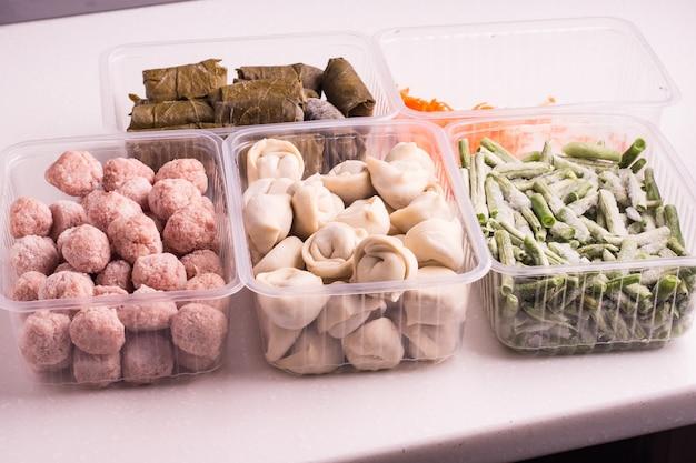 Контейнеры с замороженными овощами и мясными полуфабрикатами из холодильника. тефтели, пельмени, долма в виноградных листьях, нарезанная фасоль и тертая морковь