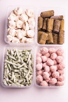 Контейнеры с замороженными овощами и мясными полуфабрикатами из холодильника. тефтели, пельмени, долма в виноградных листьях, нарезанная фасоль