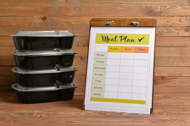 Контейнеры со здоровой пищей и планом питания на деревянном