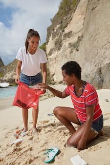 Contaminazione e concetto di ambiente. amichevoli volontari femminili interrazziali attivi trasportano rifiuti sulla spiaggia sabbiosa durante la giornata di sole