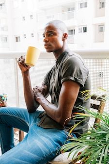 Contemplated african young man sitting in the balcony holding cup of coffee