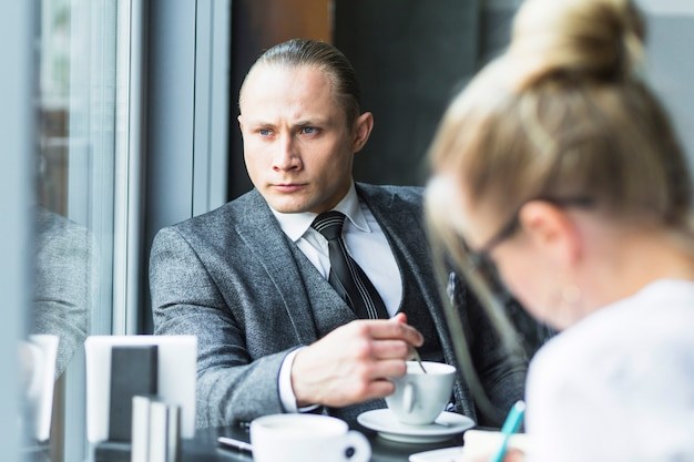 Contemplated businessman with cup of tea sitting in restaurant