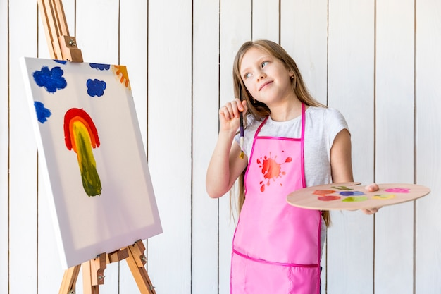 Contemplated girl holding palette and paintbrush in hand standing near the easel