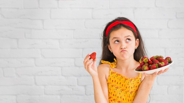Contemplated girl holding plate of red strawberries