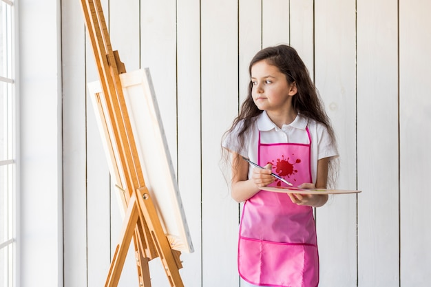 Contemplated little girl with pink apron holding paintbrush and palette