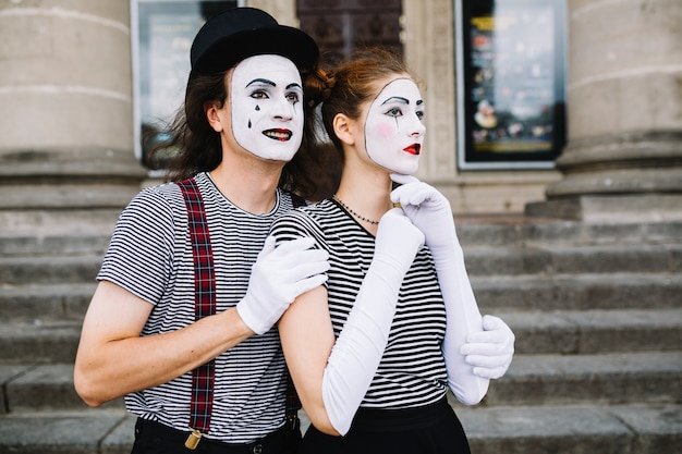 Contemplated mime couple standing in front of staircase