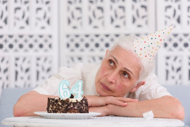 Contemplated senior woman resting her head on table near birthday cake