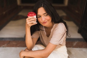 Contemplated smiling girl holding take away coffee cup