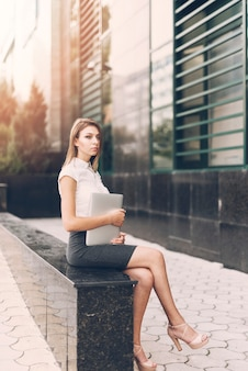Contemplated young businesswoman holding digital tablet sitting on marble bench