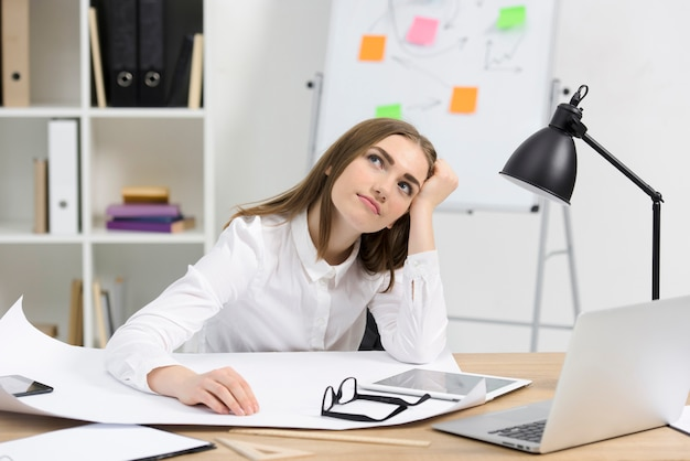 Contemplated young businesswoman with white paper; eyeglasses and digital tablet on wooden desk