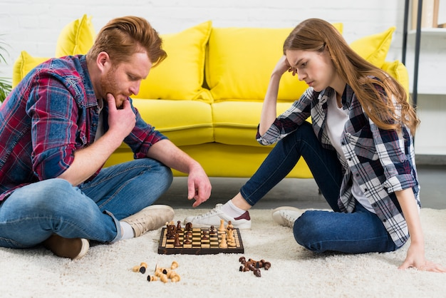 Contemplated young couple looking at chess game in the living room