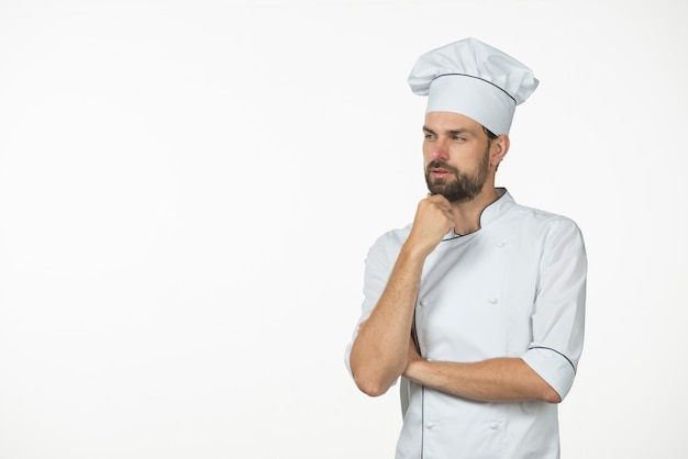 Contemplated young male chef isolated on white background