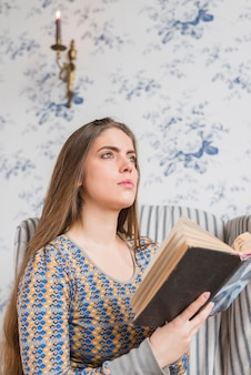 Contemplated young woman holding book in hand looking up
