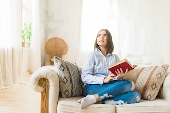 Contemplated young woman holding book sitting on sofa