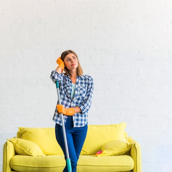 Contemplated young woman holding mop standing in front of yellow sofa against wall