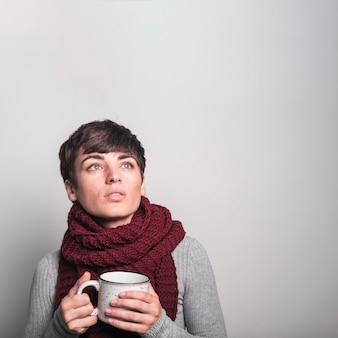 Contemplated young woman holding white coffee mug against gray background