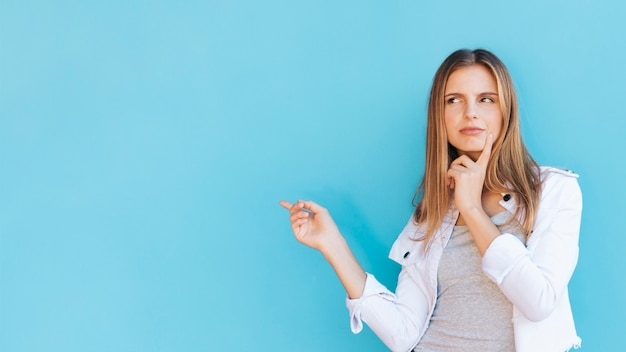 Contemplated young woman pointing finger against blue background