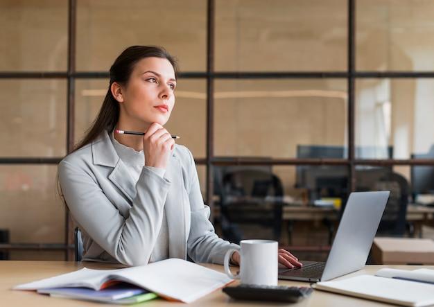 Созерцая коммерсантка сидя перед компьтер-книжкой в офисе